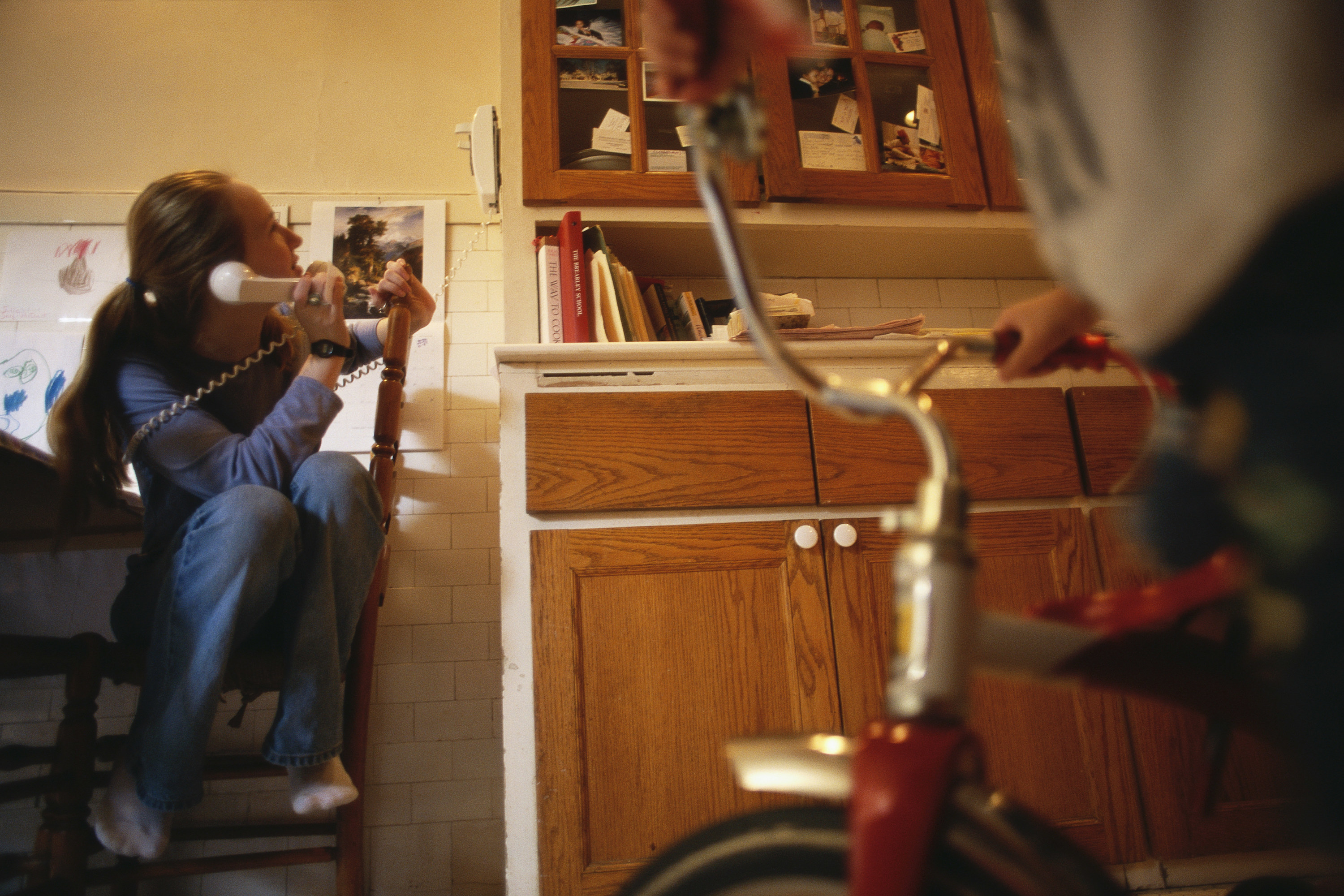 Photo of a teen girl talking on the phone in her family's kitchen