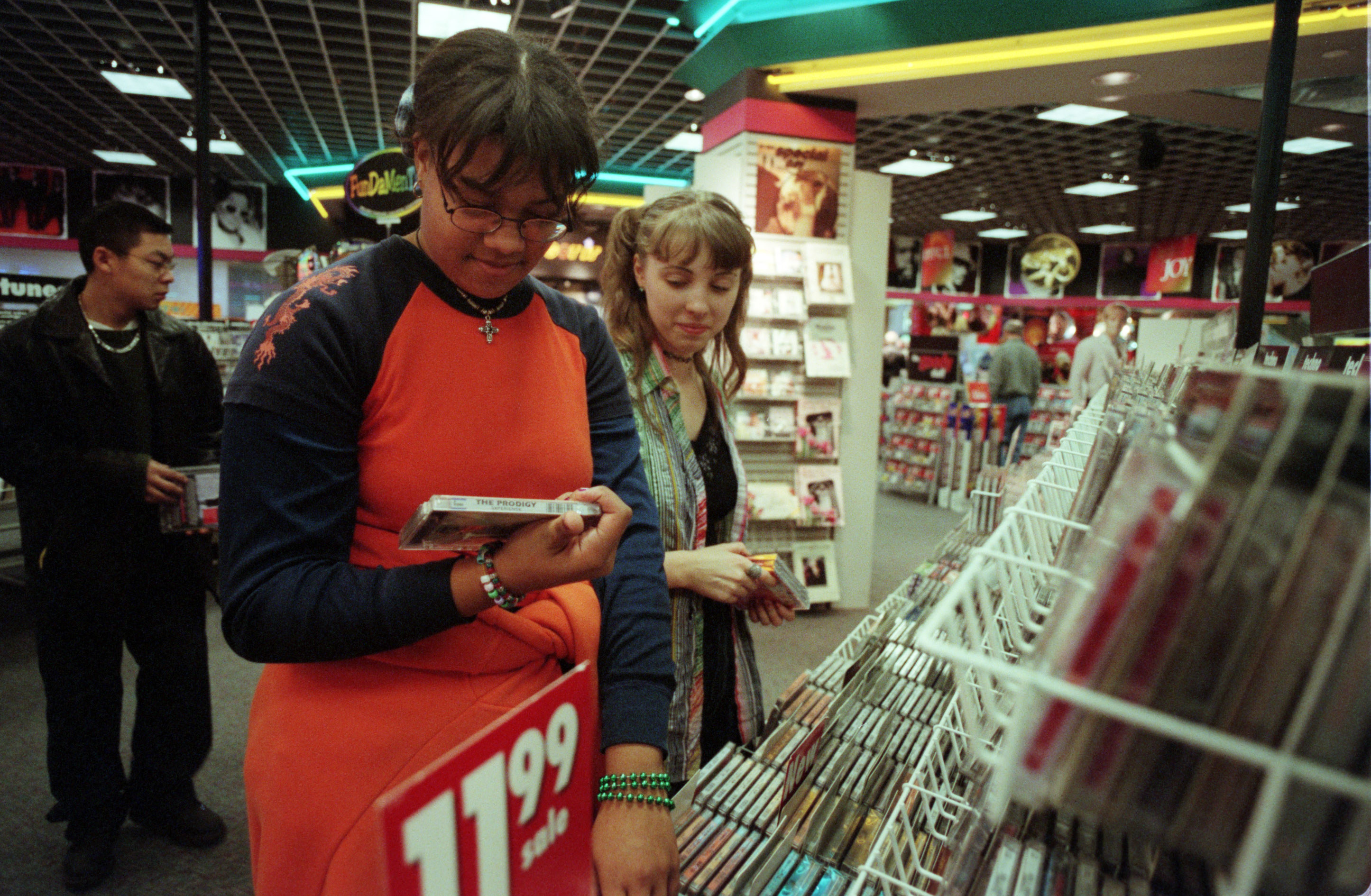 Photo of two kids looking at a CD in a Sam Goody's