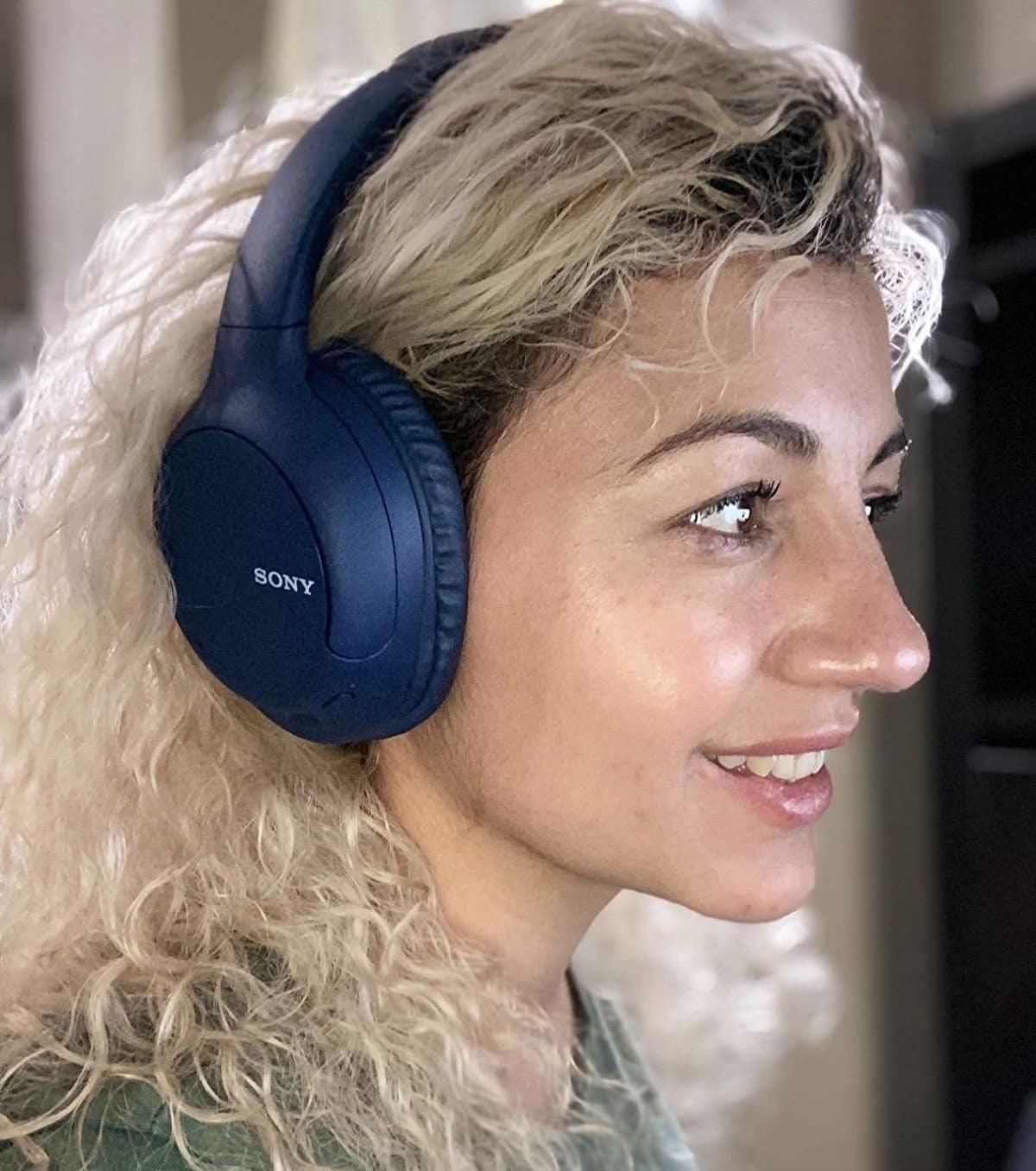 Reviewer is wearing dark blue headphones