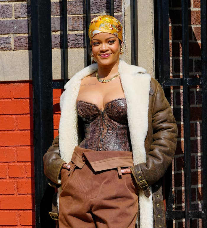 Rihanna with her hands in her pockets and wearing a snakeskin print bustier, coat and a silk bandanna