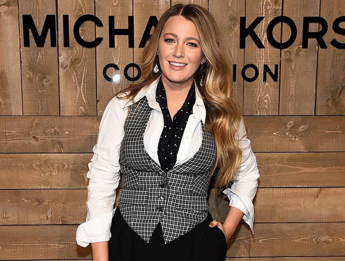 Blake smiles while wearing a plaid vest and white button down