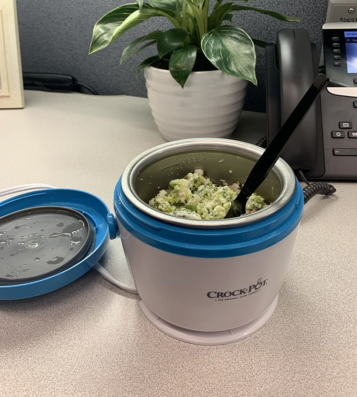 A reviewer photo of a white and blue mini crockpot with breakfast inside it sitting on a cubicle desk