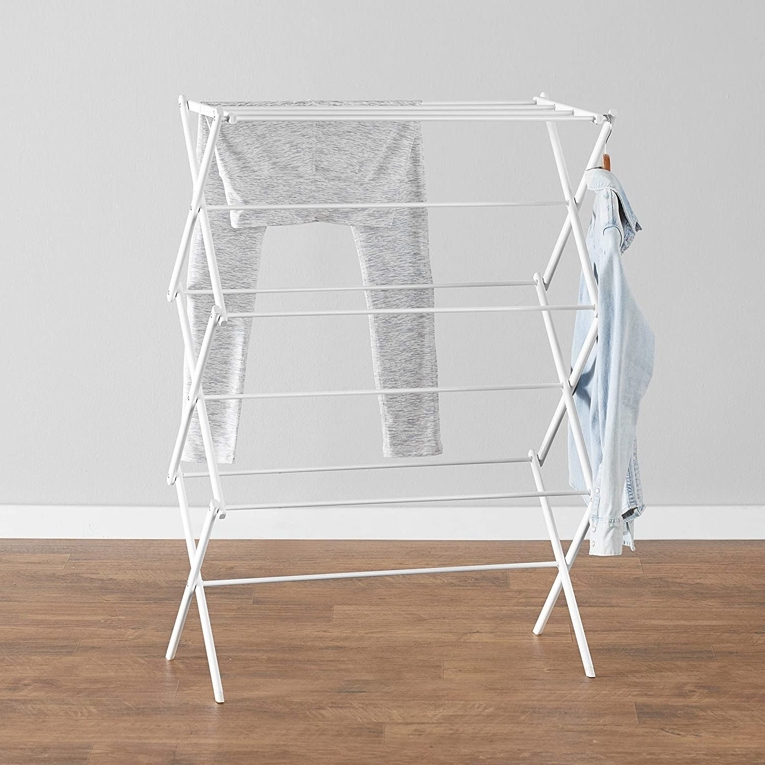 a product shot of the laundry rack in white with clothes hanging on it