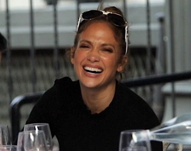 Jennifer gives a big smile while sitting at a dinner table