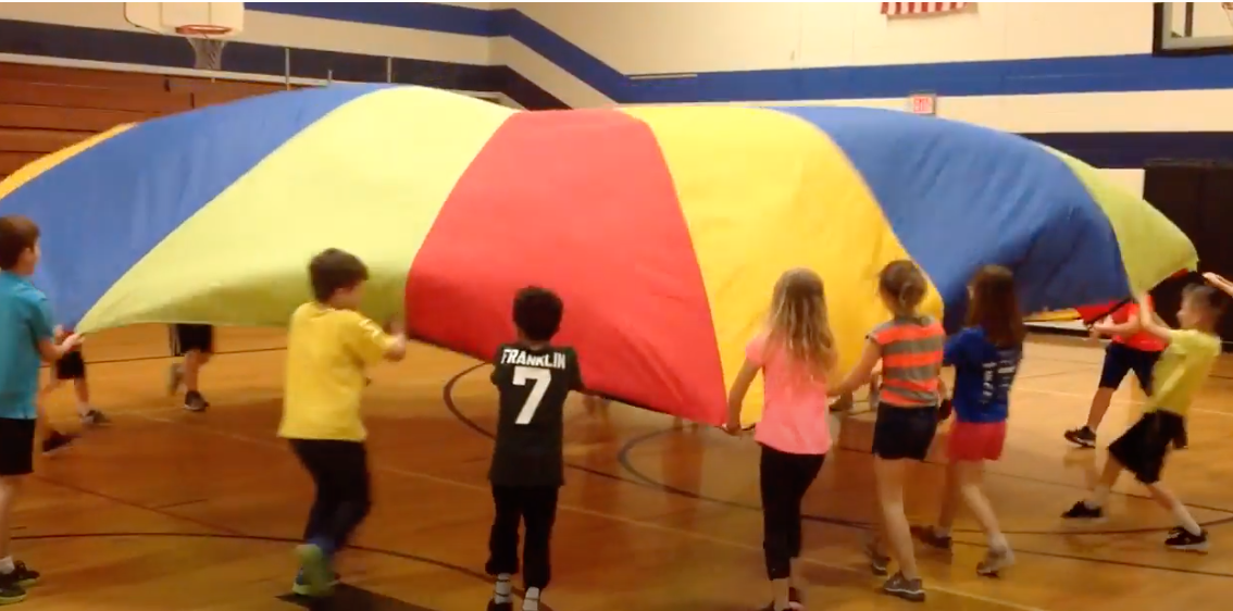 Screenshot of kids playing the parachute game in a gym