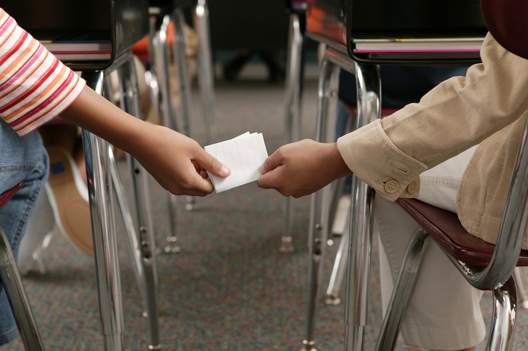 Stock image close up of two kids passing a note in class