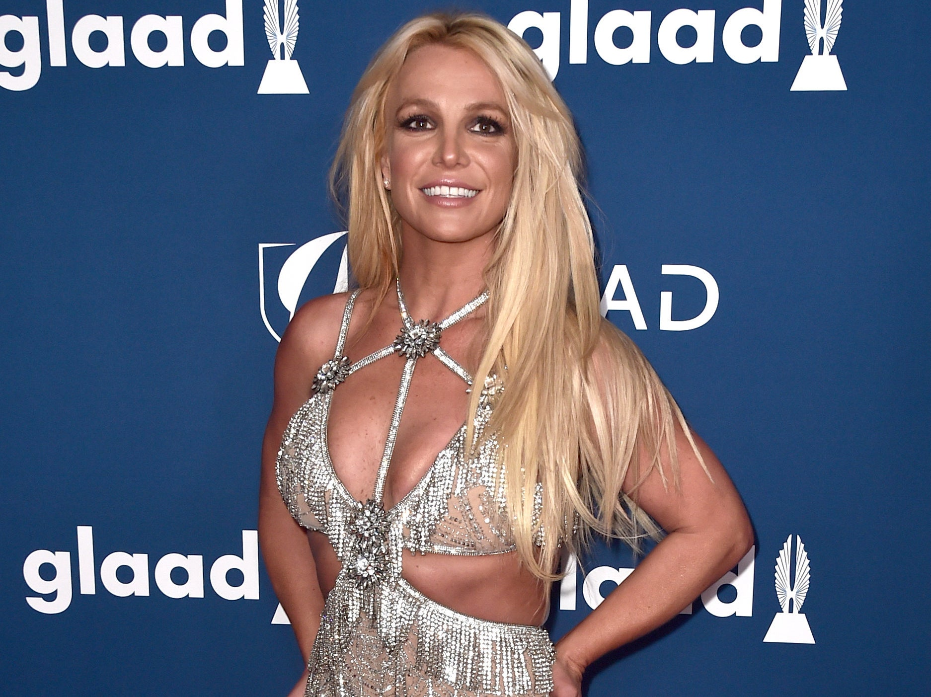 Britney smiles while wearing a cutout dress with diamond fringe