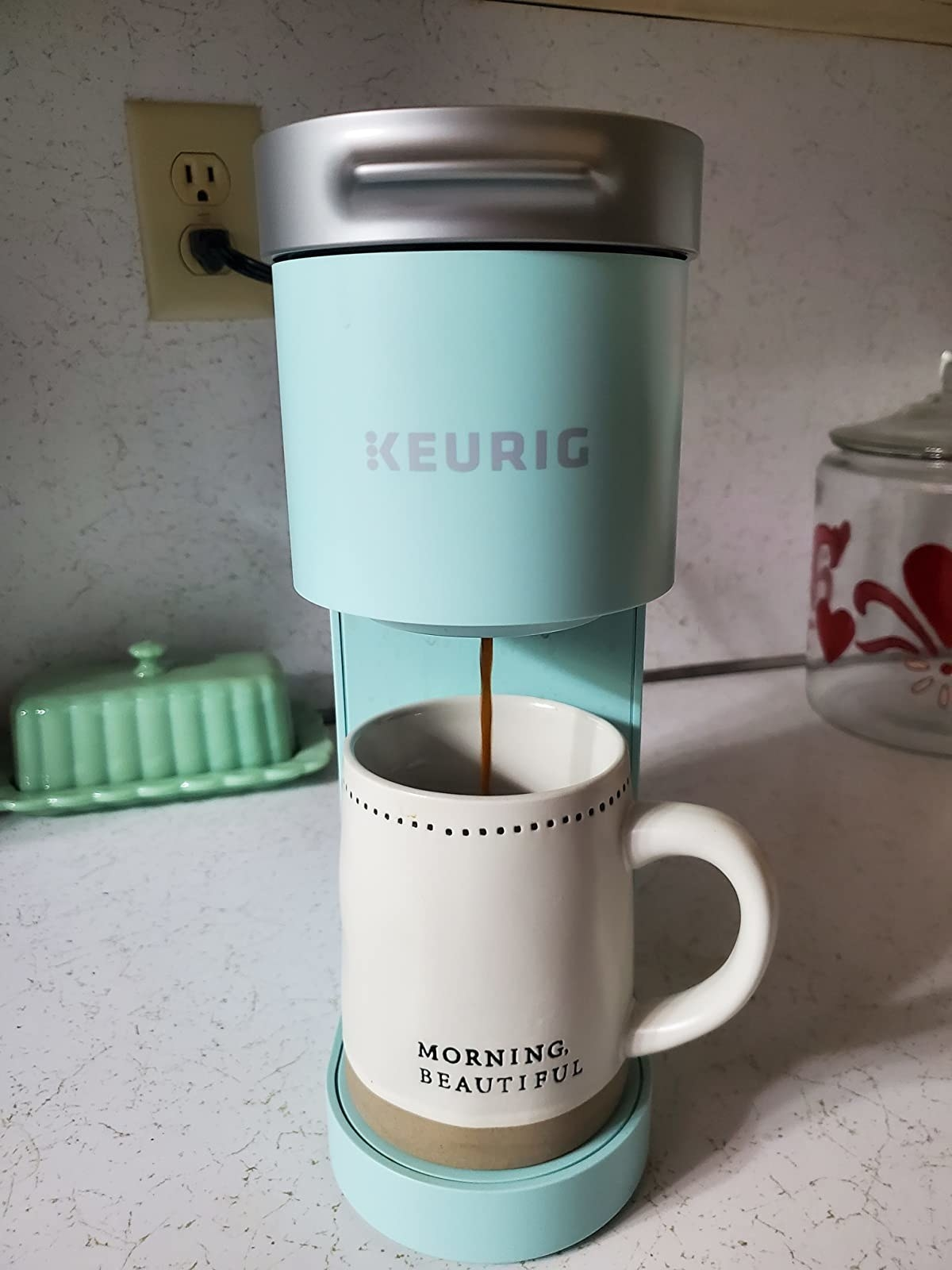 a reviewer photo of the keurig coffee maker with a coffee cup inside ready for the coffee to pour