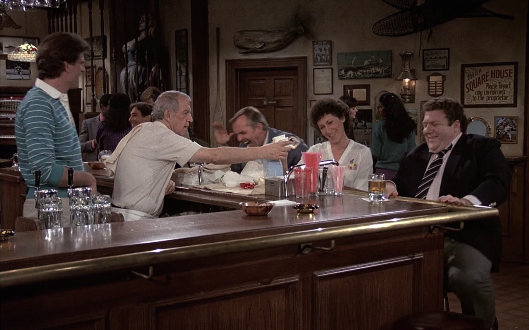 """The """"Cheers"""" gang sits around the bar, laughing"""