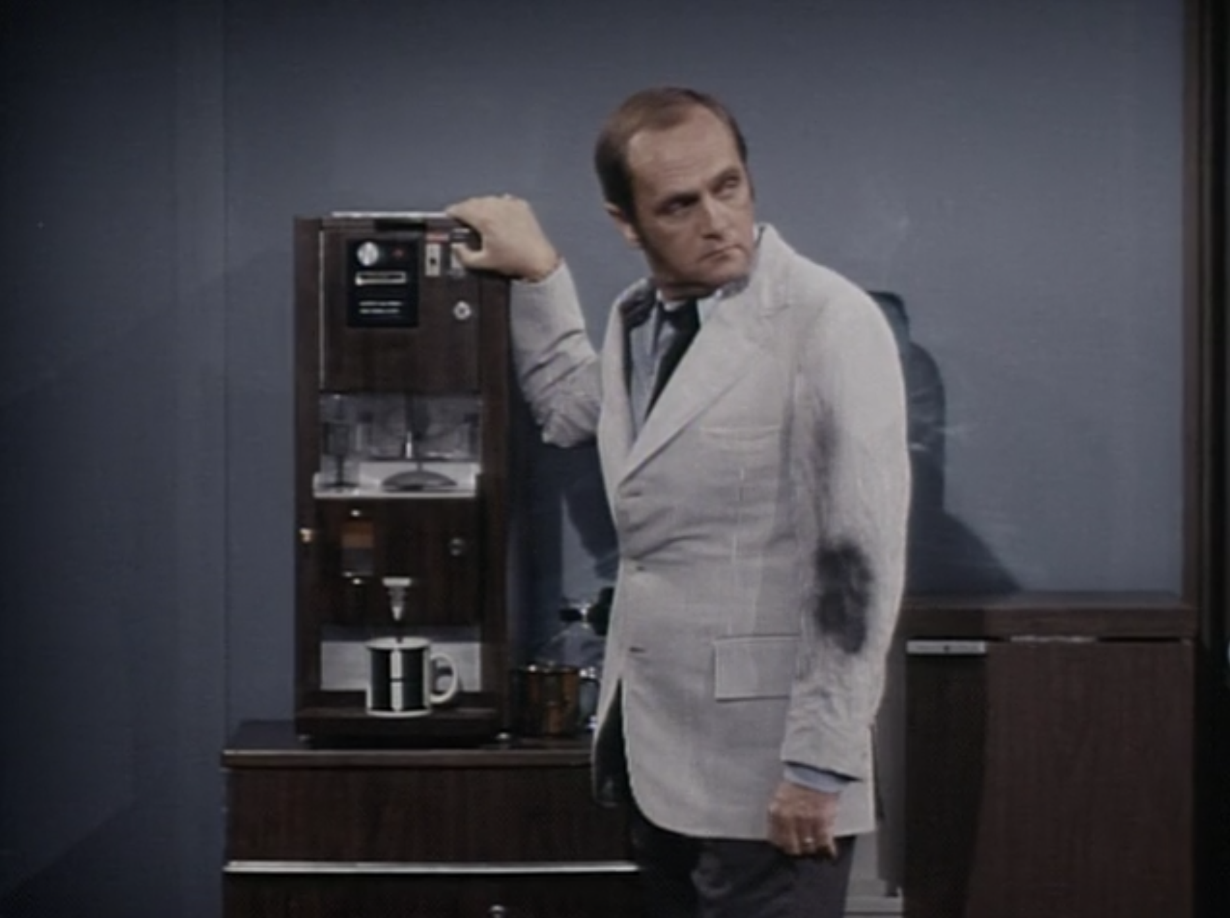 Bob Newhart standing in front of a coffee machine as Dr. Robert Hartley