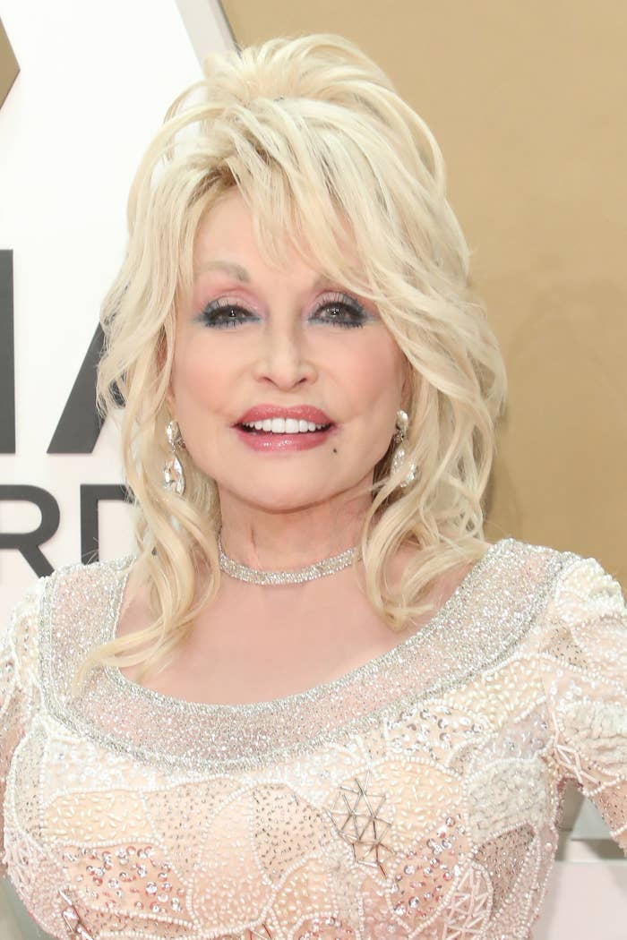 Dolly Parton smiles at a red carpet event while wearing a dress