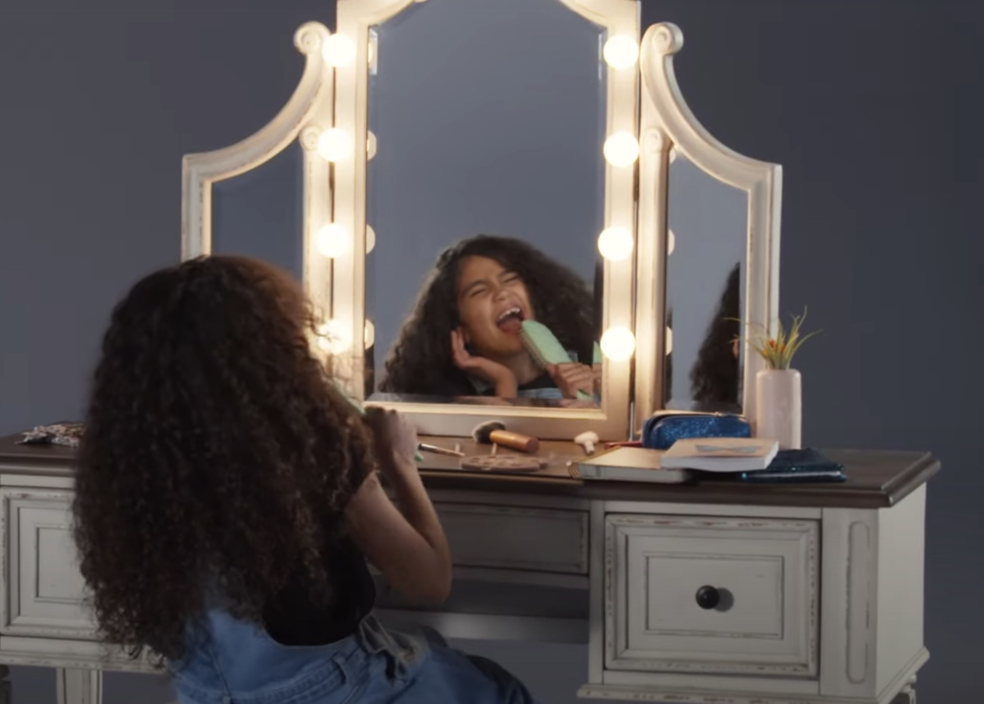 Monroe sings into a hairbrush while sitting in front of a vanity
