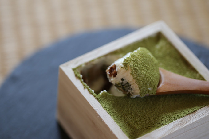 Tiny wooden spoon scooping up a bit of matcha tiramisu from a wooden box.