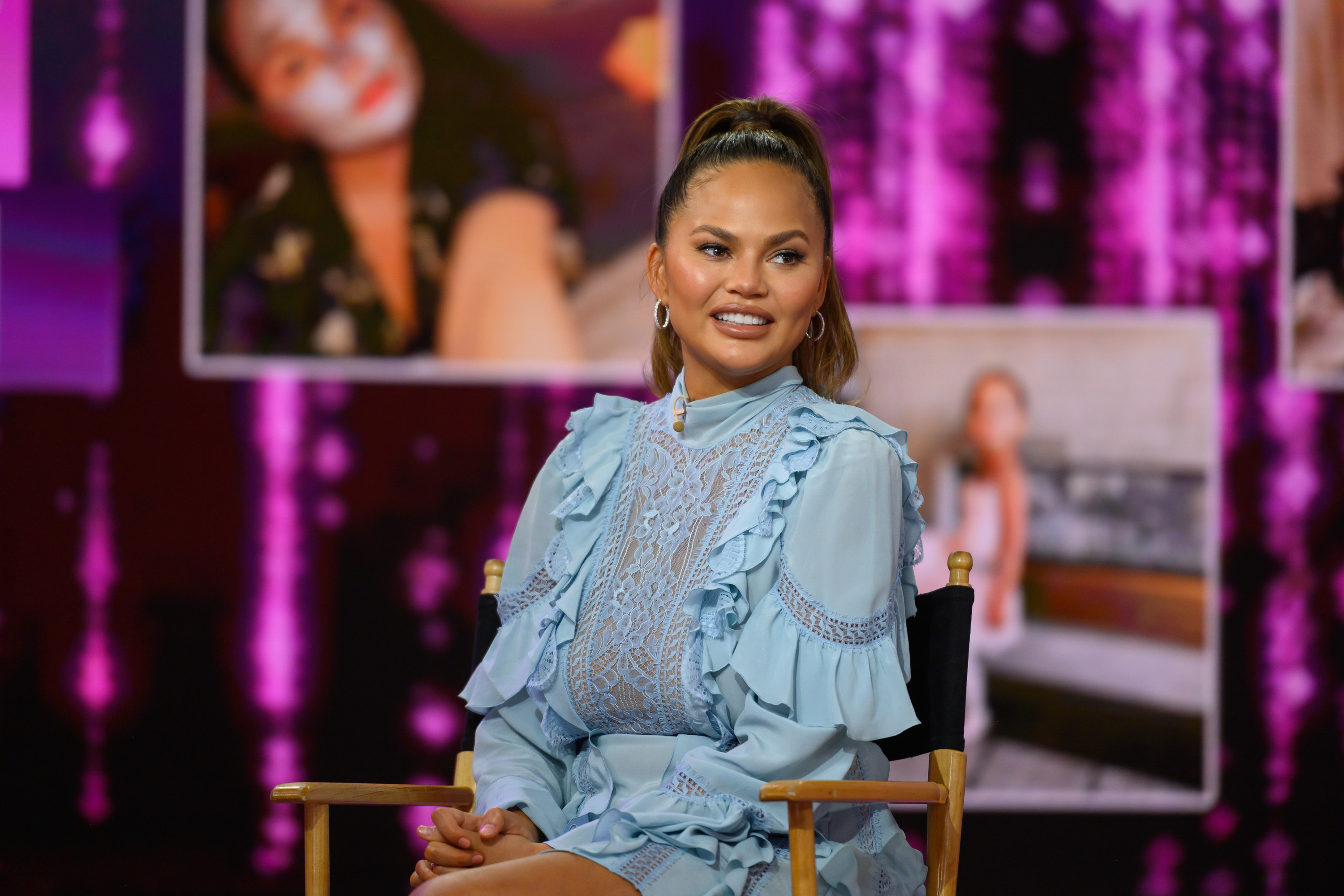 Chrissy Teigen is photographed while sitting in a chair on a set