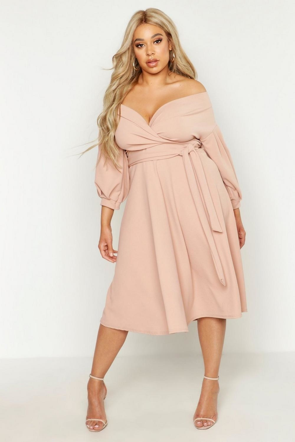 a model in the pale pink off the shoulder wrap dress