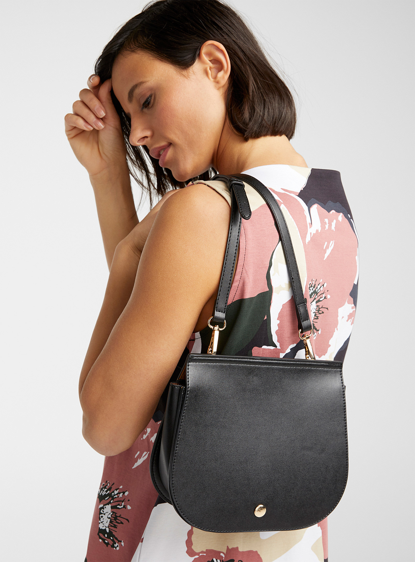 a person with the shoulder bag slung over their shoulders