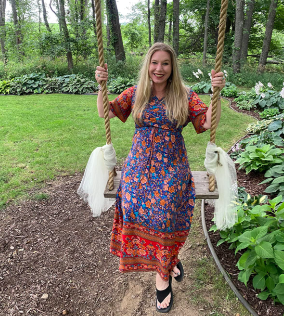A customer review photo of them wearing the dress in A-blue on a swing