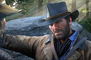 arthur morgan wears cowboy hat leans against rock