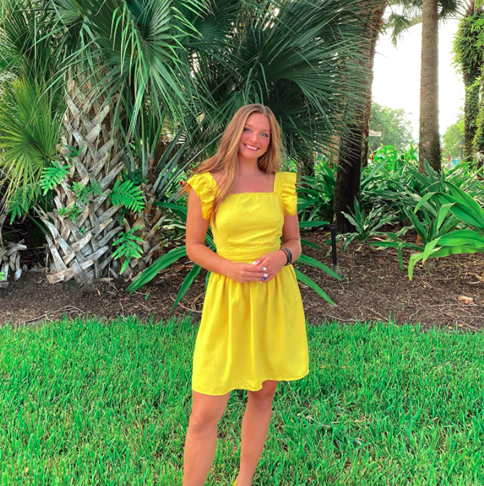 A customer review photo of them wearing the dress in yellow