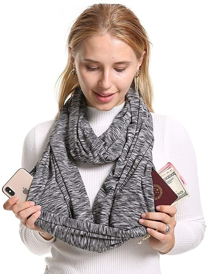person wearing looped scarf with pocket for passport and phone