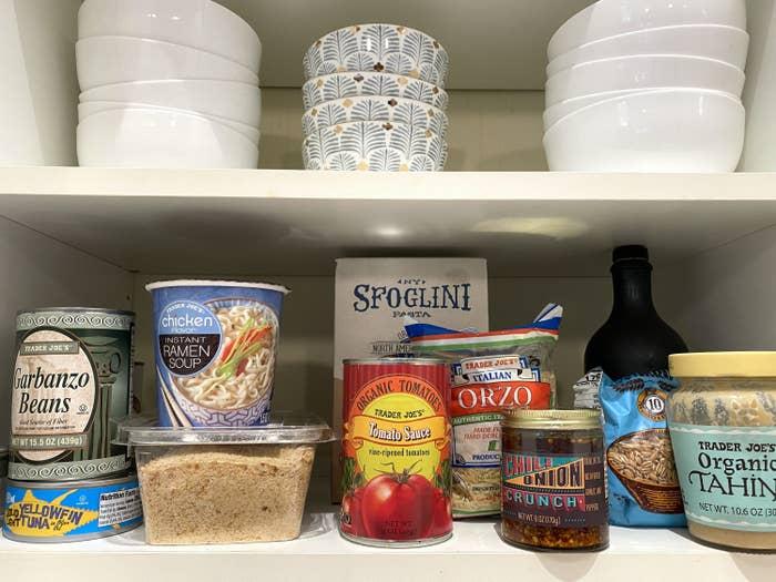 Cupboard shelves with foods like organic tahini, tomato sauce, orzo, and garbanzo beans