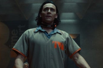 A close up of Loki as he looks upwards towards someone off screen while wearing a prison jumpsuit