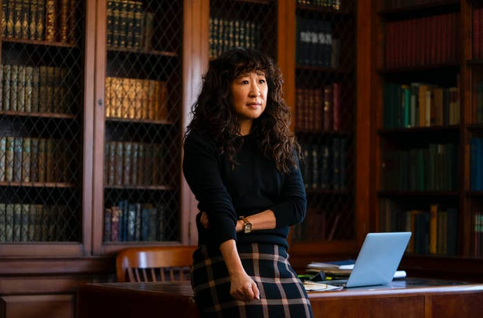 Sandra Oh leaning against a desk