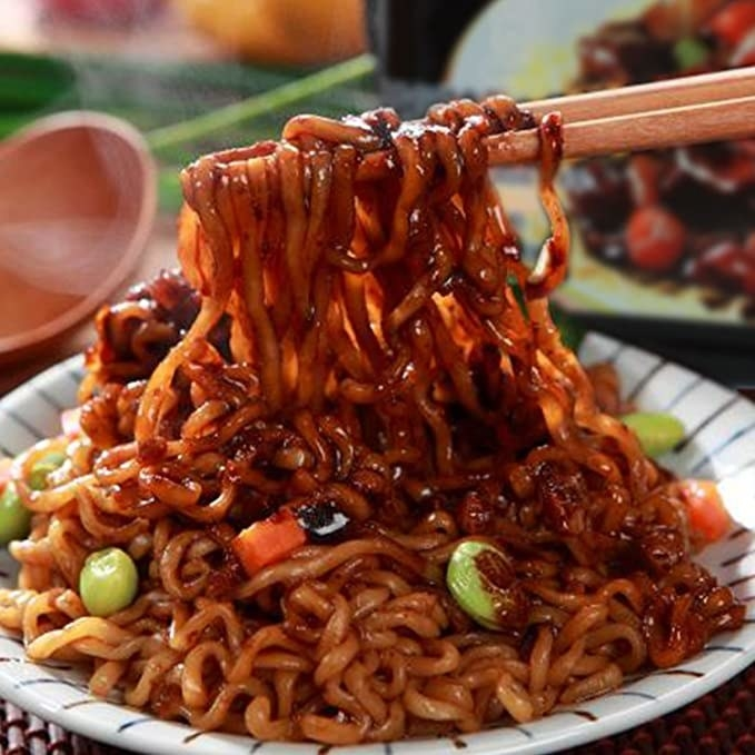 A bowl of noodles laden with sauce, peas, and carrots