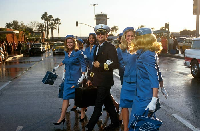 Leo's character crossing the street with flight attendants on his arms
