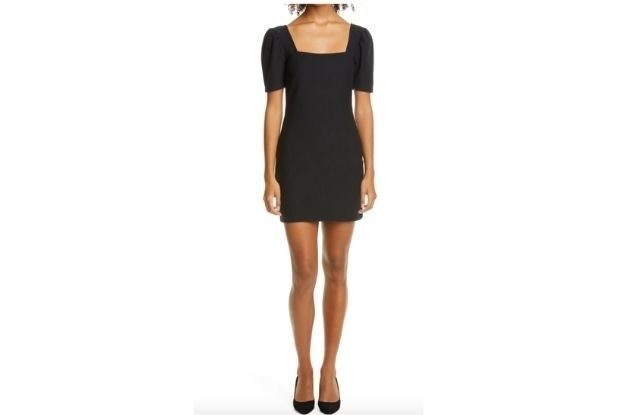 Model wearing a black dress with heels