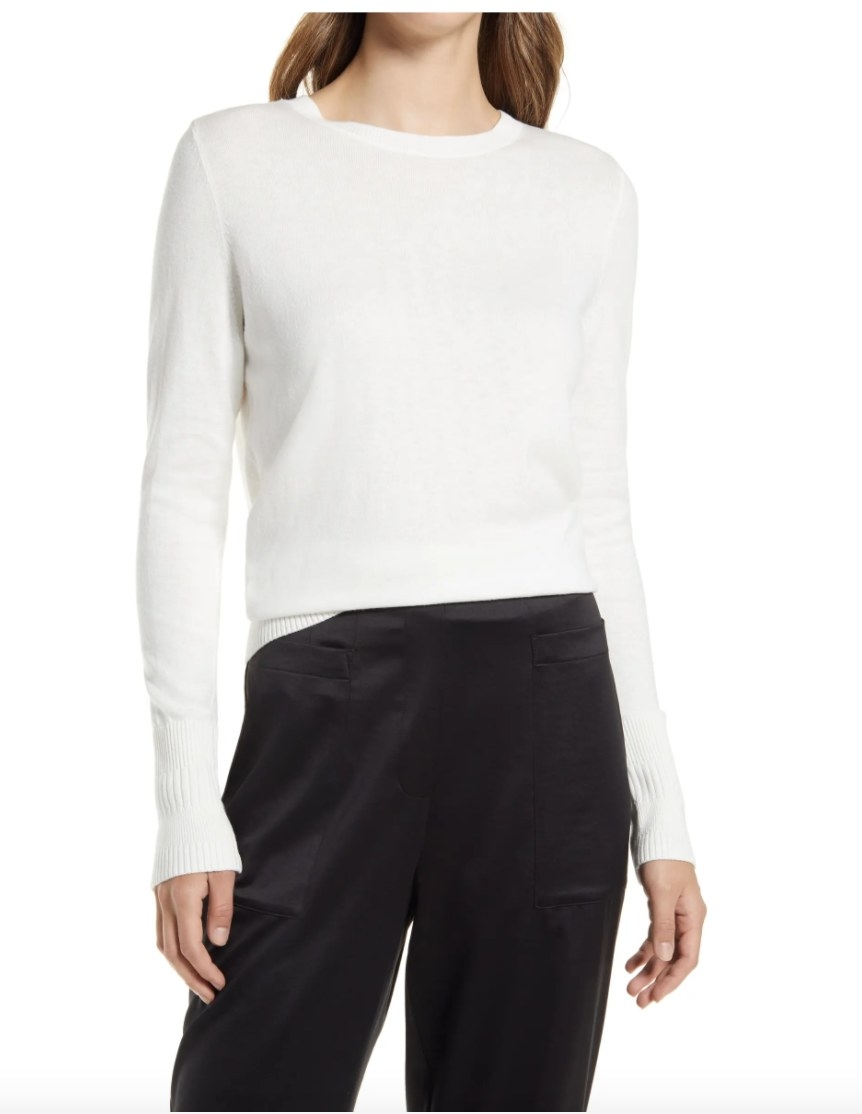 Model wearing a white crewneck top and black pants