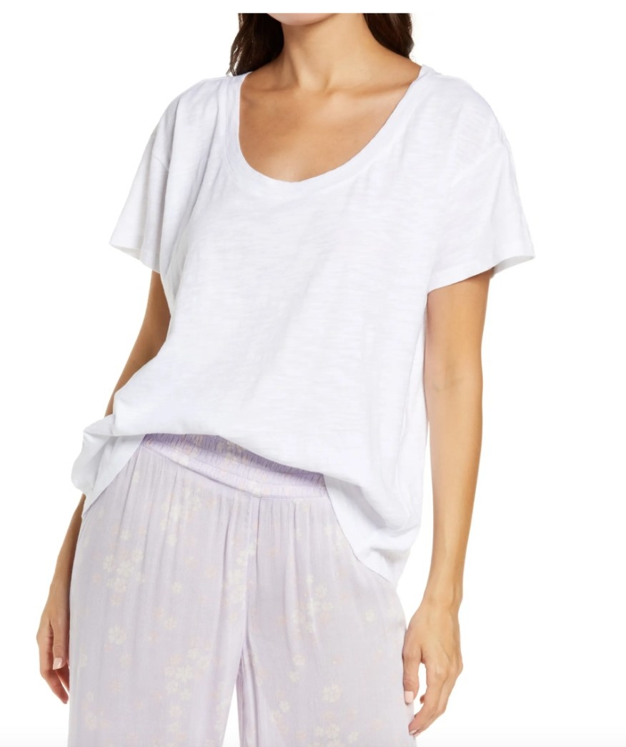 Model wearing a white tee shirt with purple pants