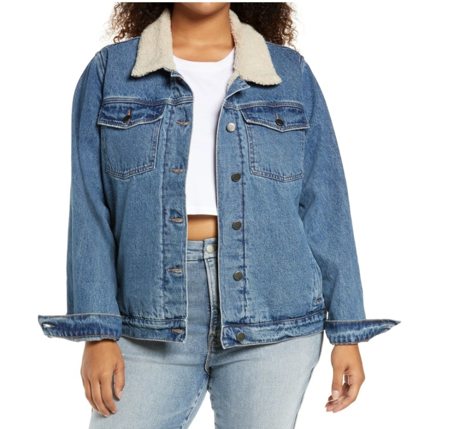 Model wearing denim jacket with white collar, white top and jeans