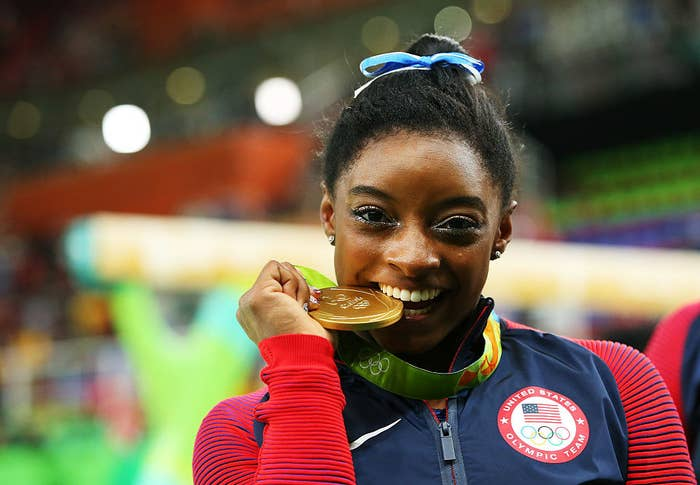Simone Biles taking a bite out of her gold medal