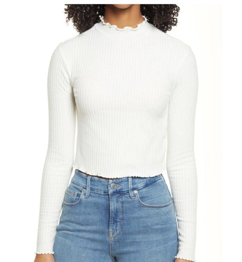 Model wearing white lettuce hem mock neck top with jeans