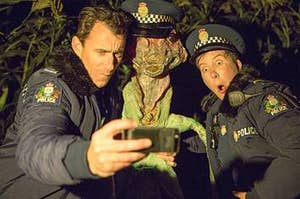 A man and a woman taking a selfie with an alien plant