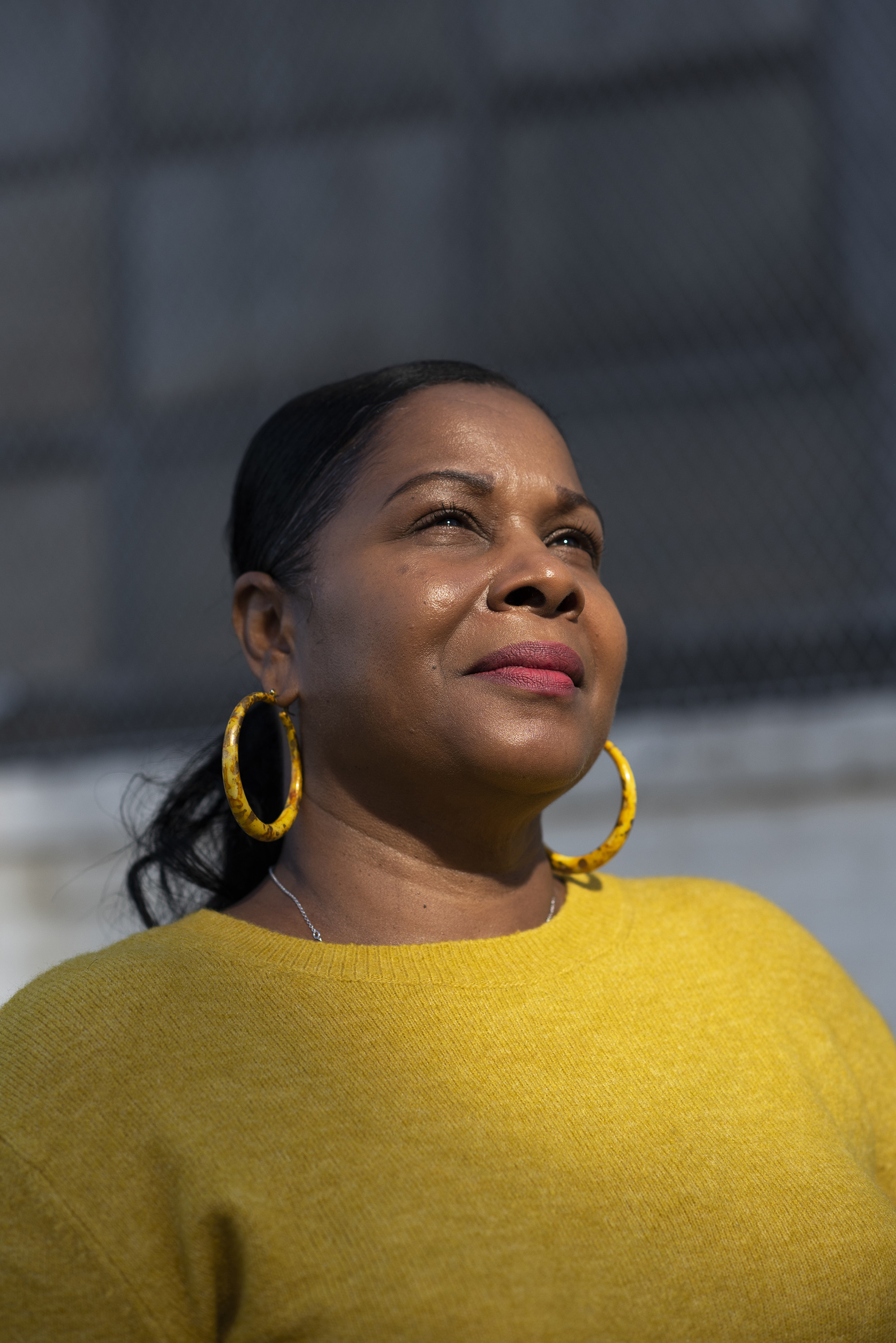 A woman in a sweater and matching hoop earrings faces into the sun