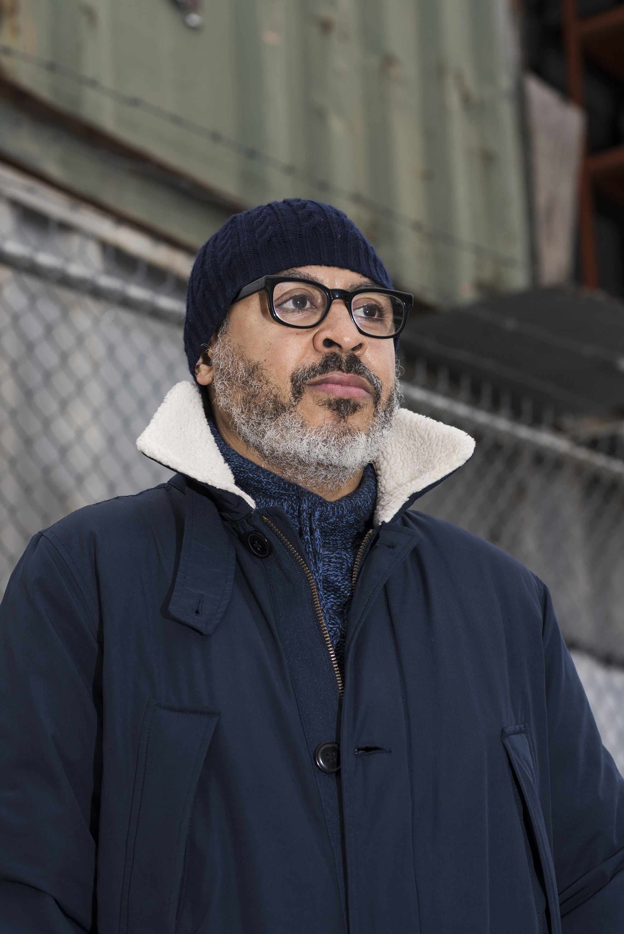 A man with glasses in a jacket looks off past the camera
