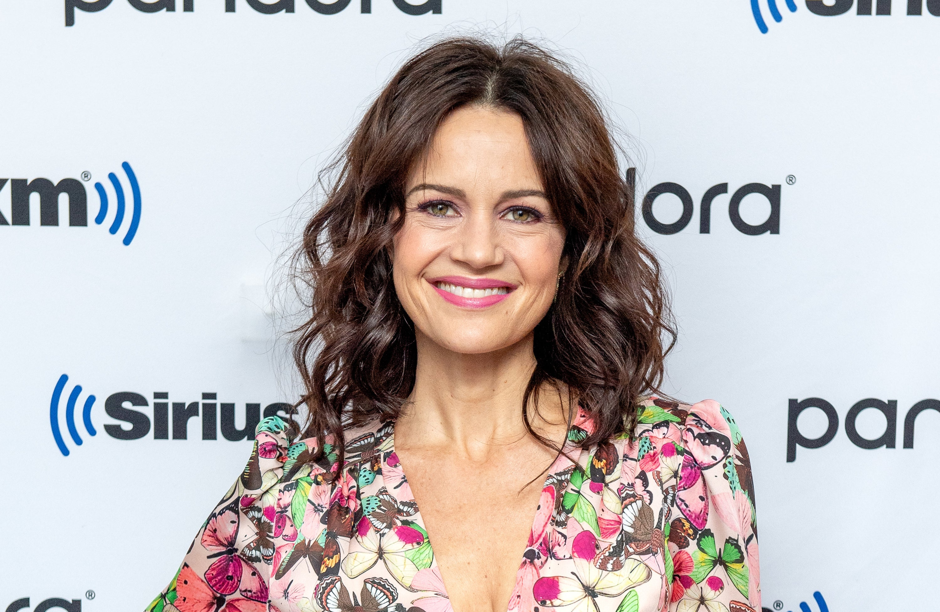 Photo of Carla Gugino smiling at the camera in a floral dress from the neck up