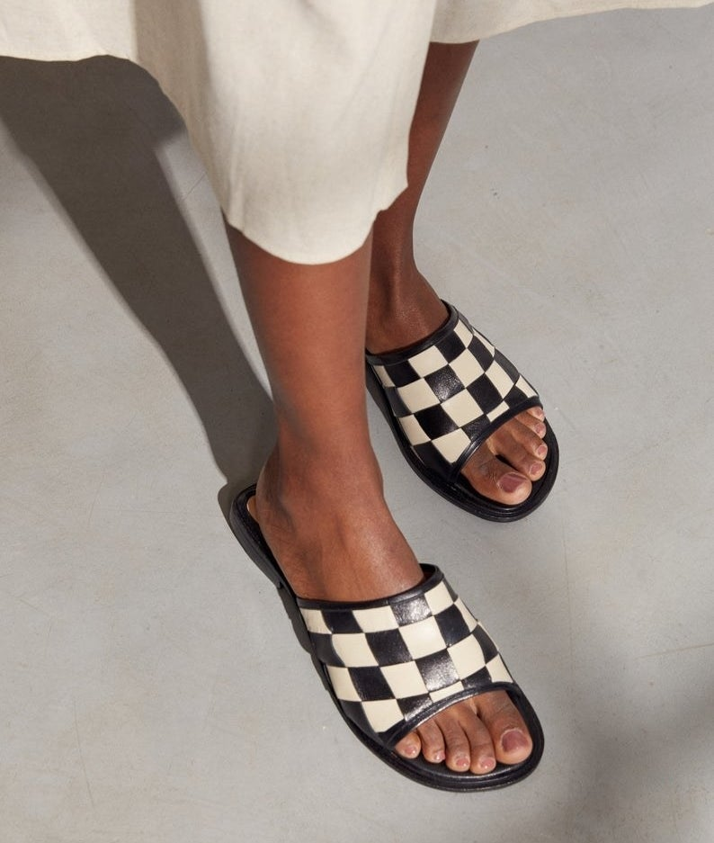 a mode wearing a white skirt and a pair of black and white gingham slides