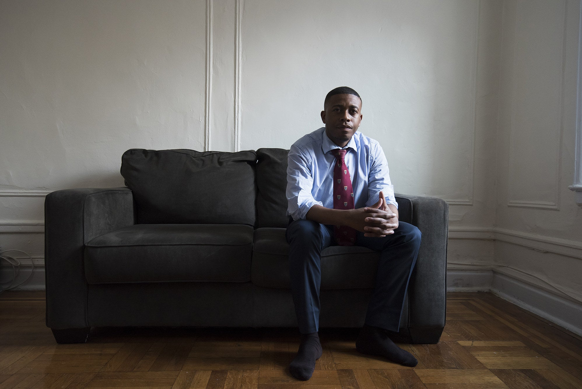 A man in a suit sits on a couch in an apartment