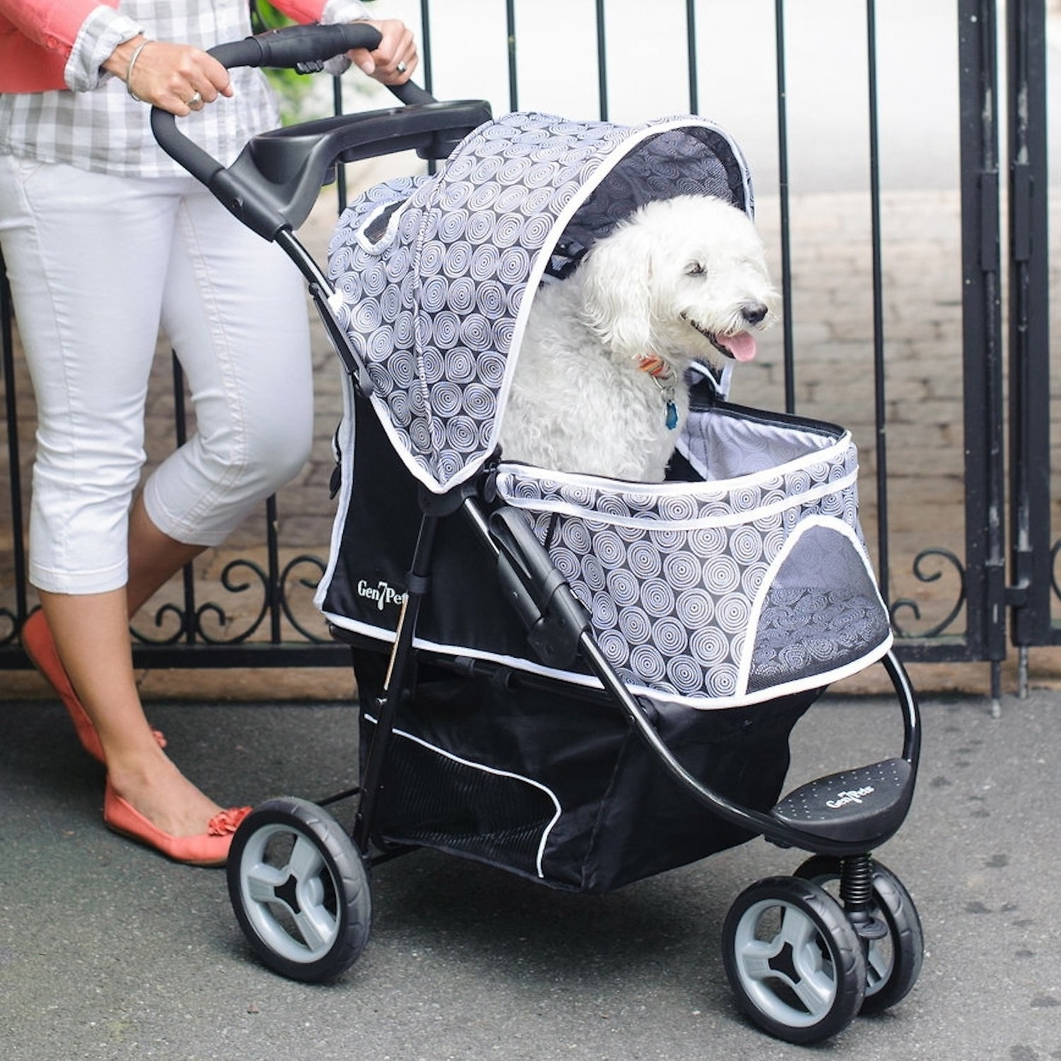 A model pushing their dog in the pet stroller with a canopy