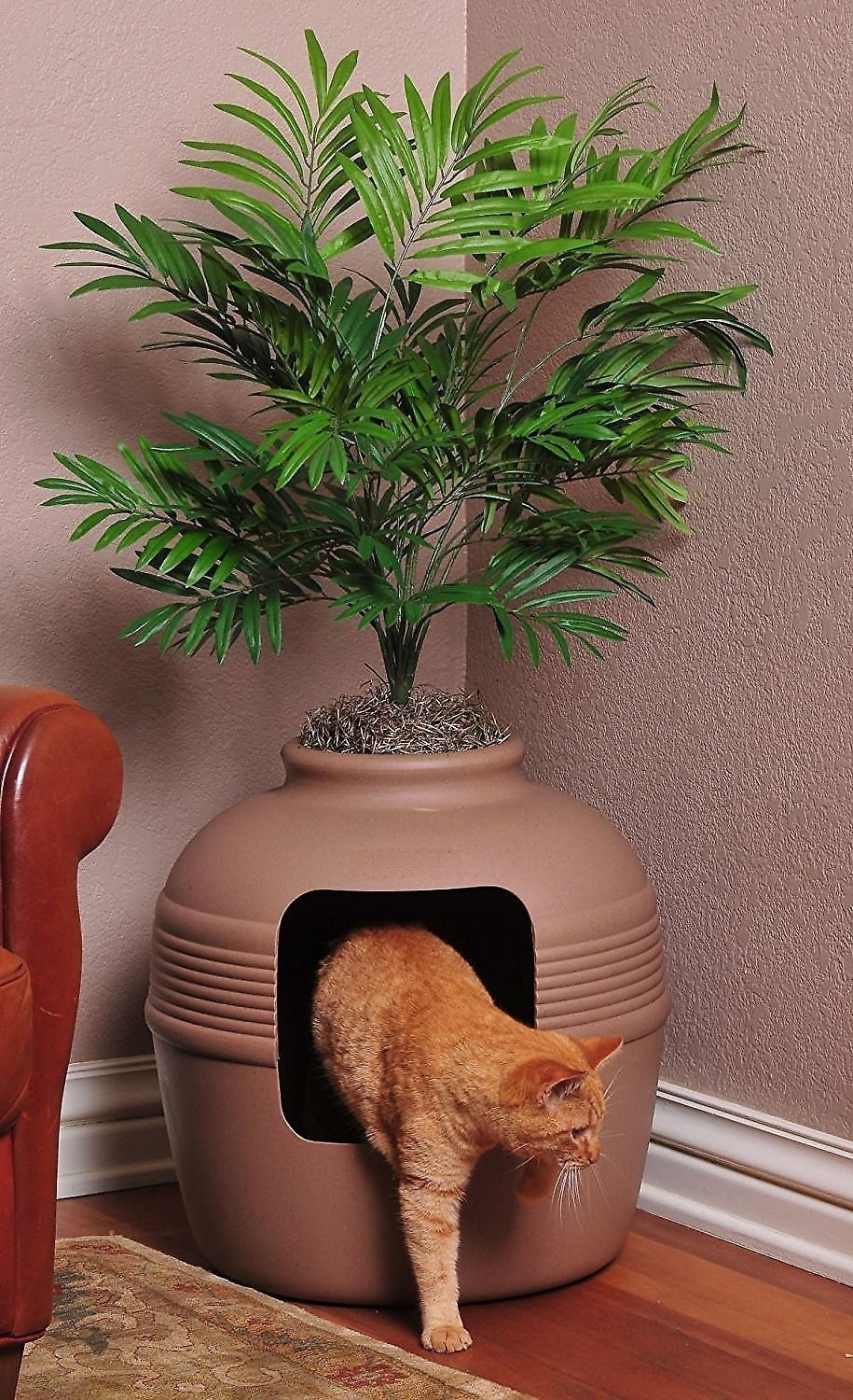 A cat leaving the litter box that's designed to look like a planter with a faux plant on top
