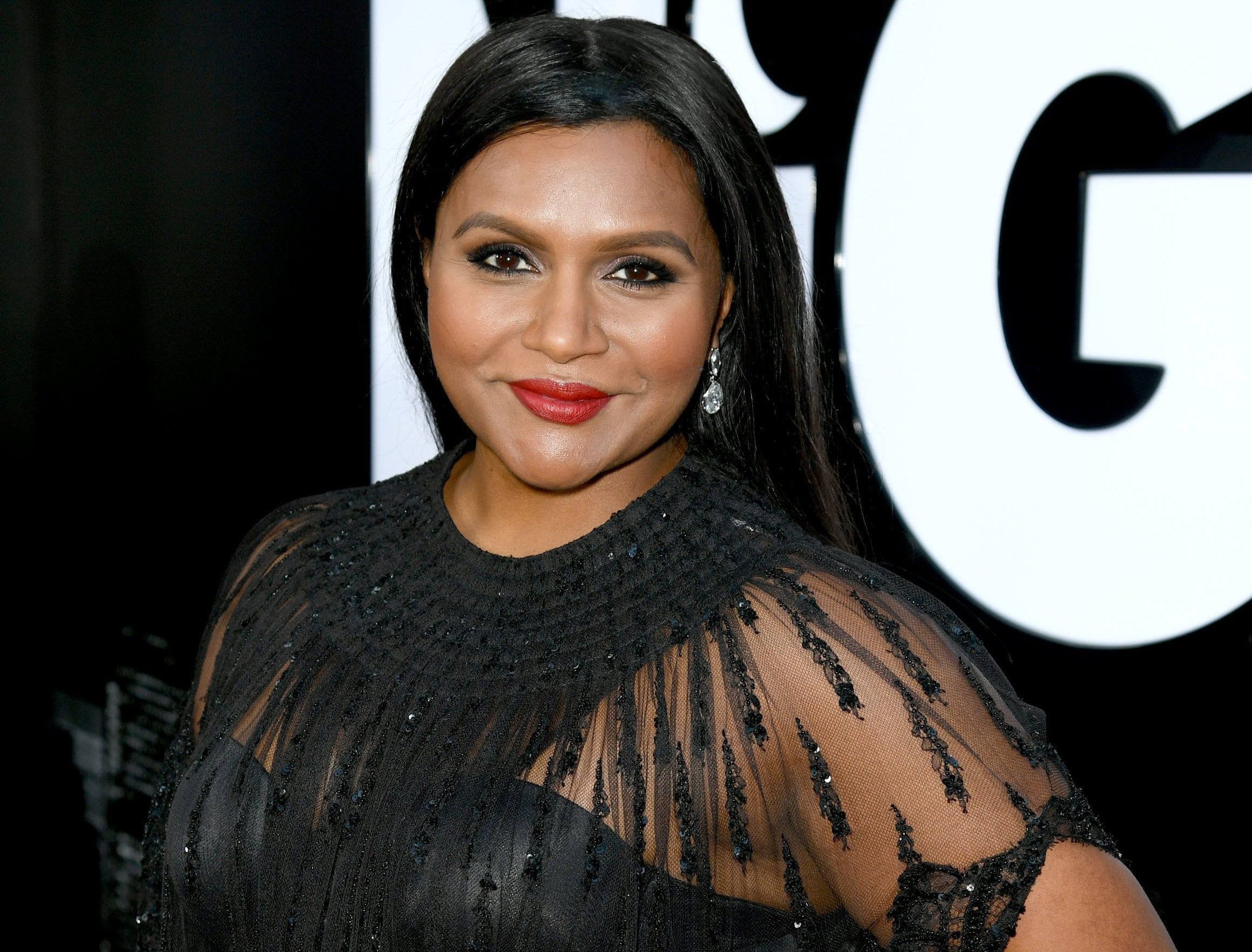 Mindy smiles in a black dress at an event