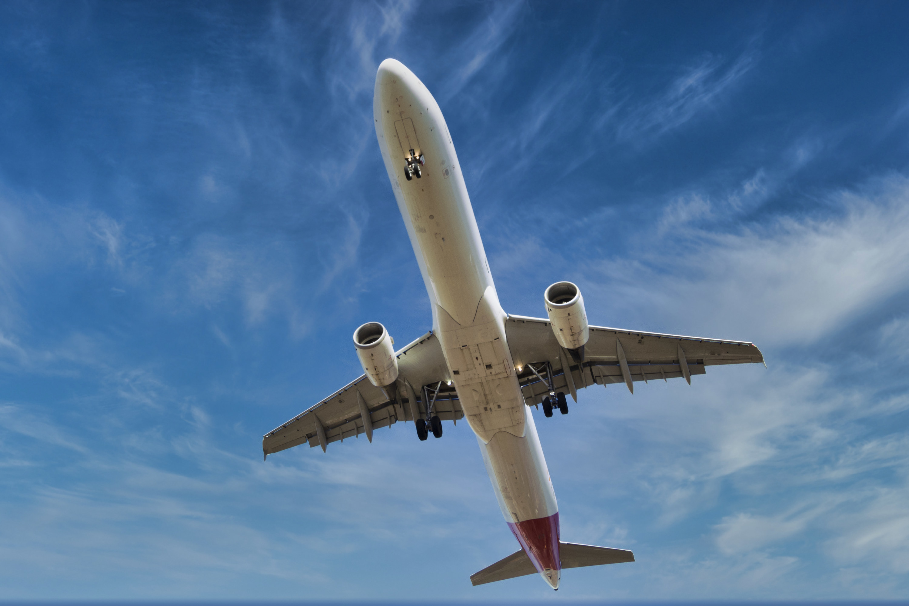 Stock photo of big plane before landing, flying in blue sky.