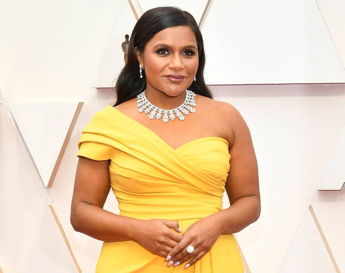 Mindy smiles on a red carpet while wearing a yellow one shoulder dress and a diamond necklace