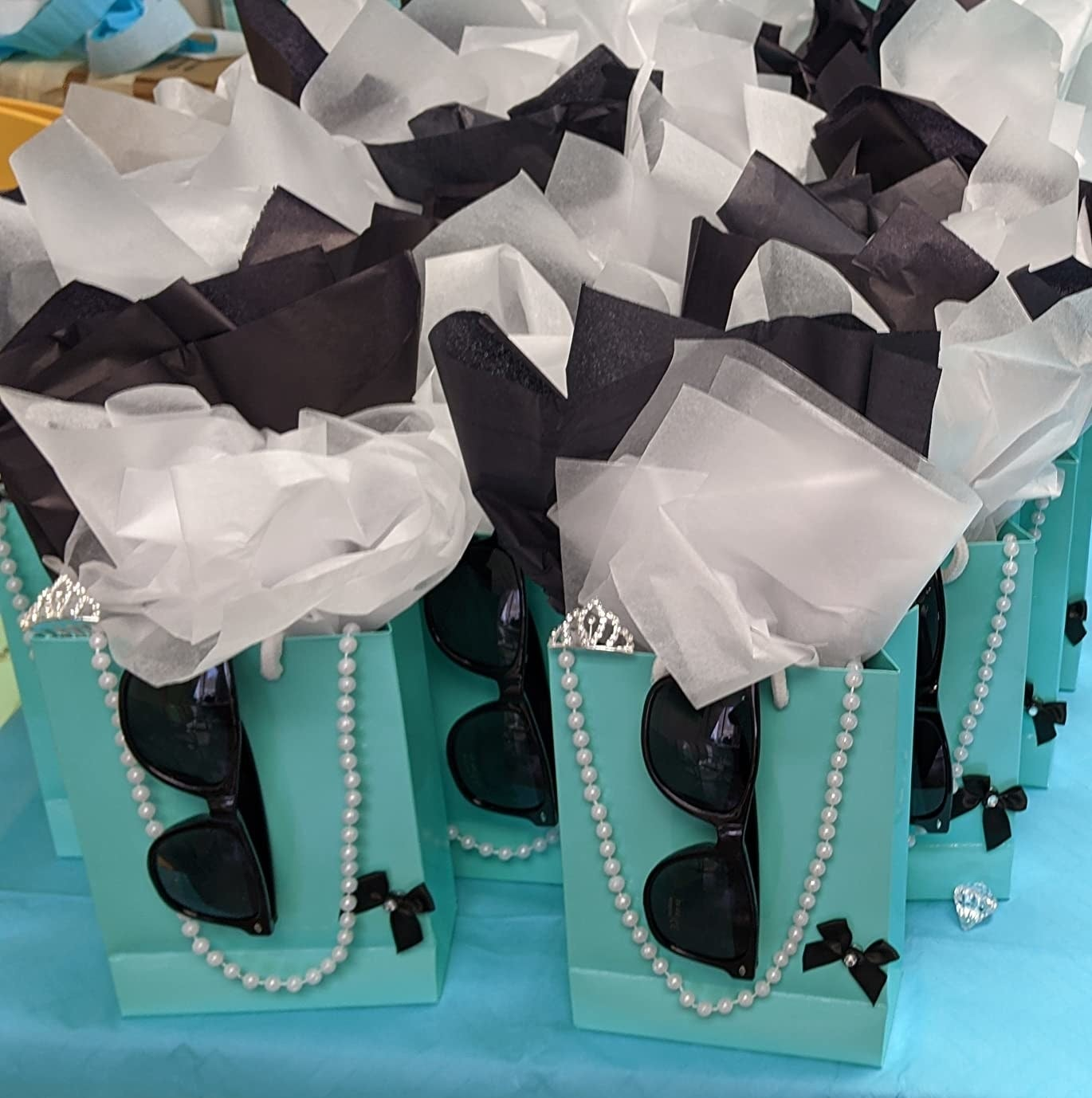 A reviewer photo of sunglasses on teal party bags with white tissues