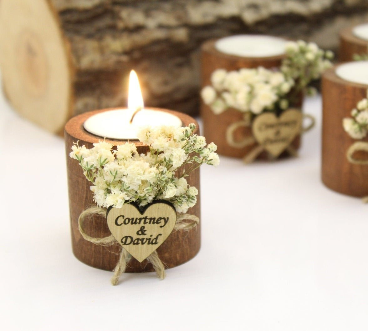 """The tea candle in a wooden votive with white flowers and a wooden heart on the front that says """"Courtney and David"""""""