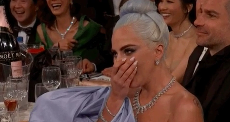 Lady Gaga covering her mouth and laughing at the Golden Globe Awards