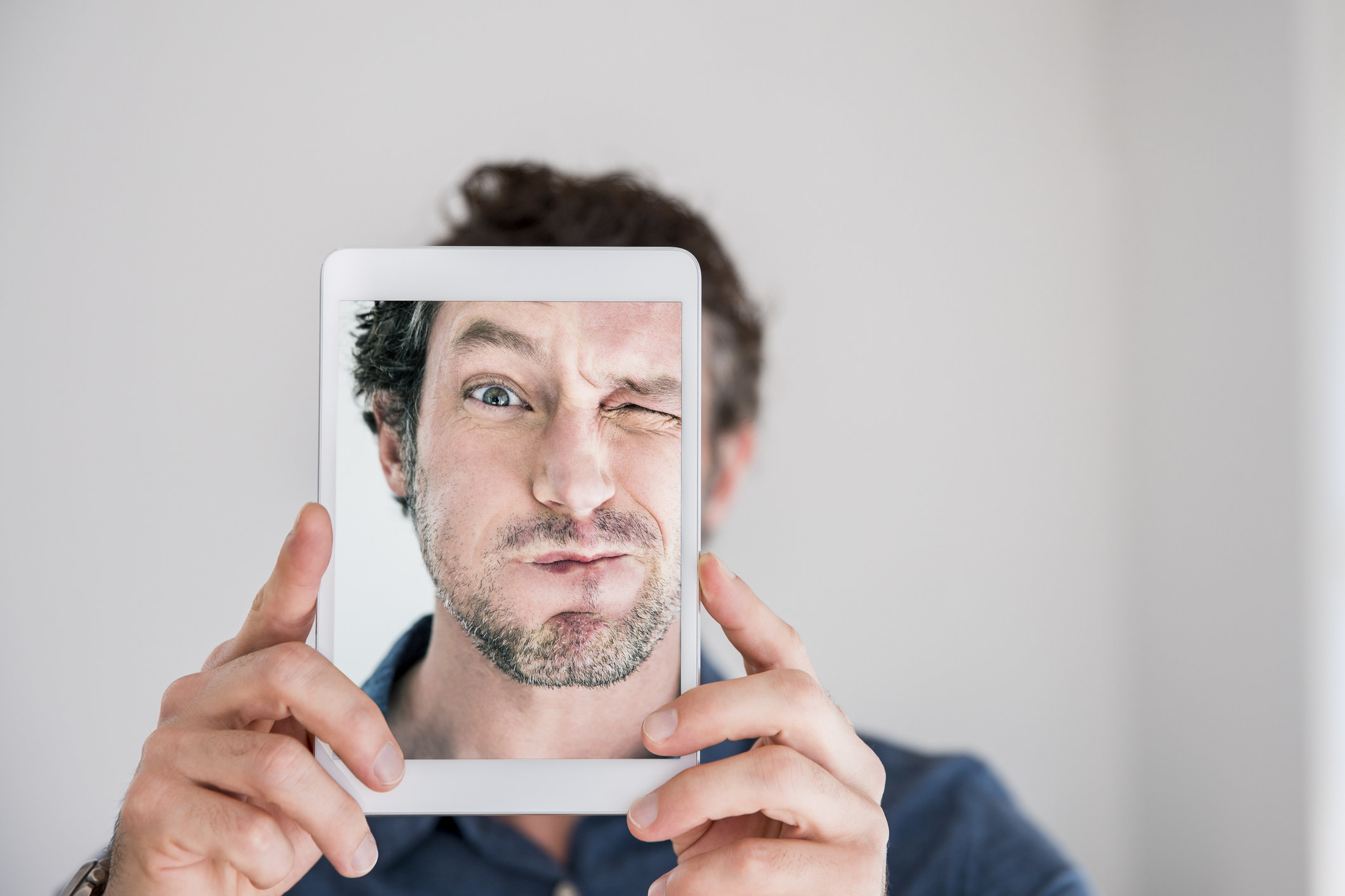 man making faces while taking selfie with iPad